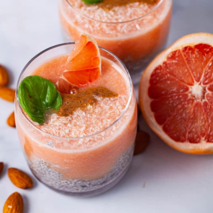 Two glasses filled with chia pudding, infused with a grapefruit sauce, topped with almond butter, Basil leaves, coconut shreds, and slices of grapefruit.