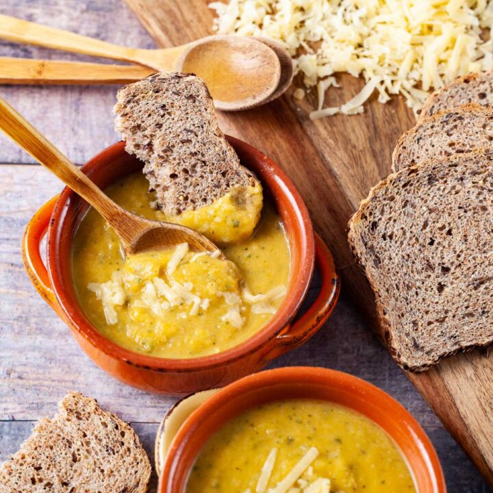 Two bowls filled with yellow squash soup, topped with Parmesan cheese and served with extra cheese and bread on the side.