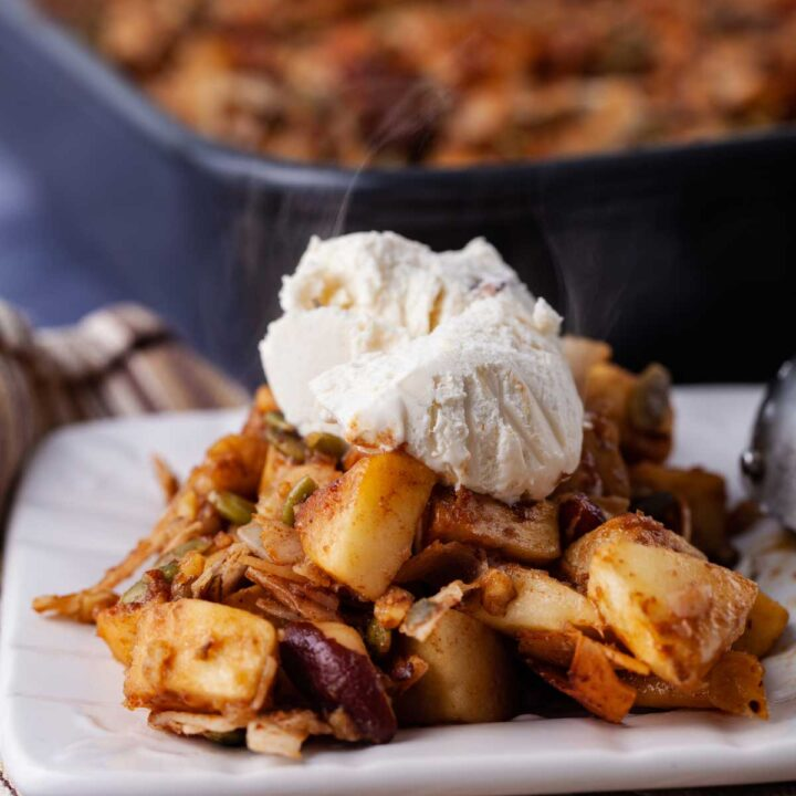 Warm apple crisp on a small plate topped with a scoop of Paleo ice cream.