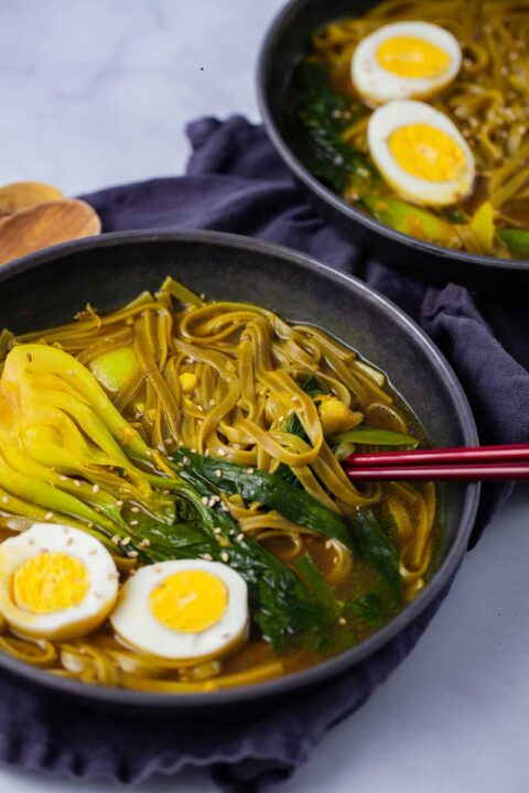Two bowls filled with bok choy noodle soup topped with two halves of a cooked egg.