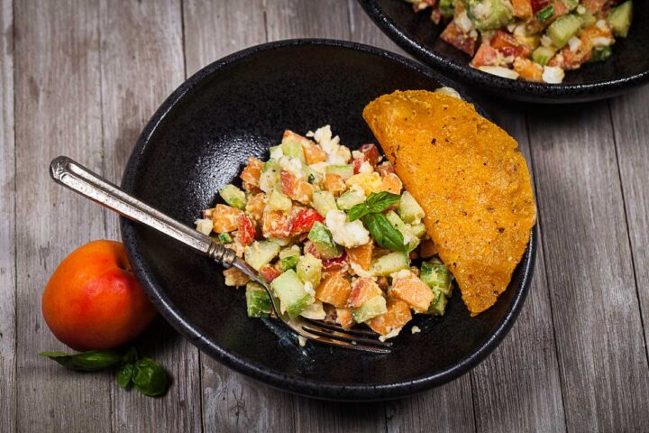A bowl filled with a healthy egg salad and apricots with a taco on the side and a fork.