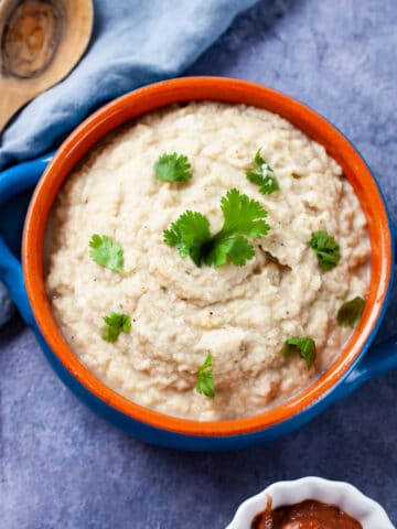 A terra cotta bowl filled with creamy mashed cauliflower and garnished with Parsley.