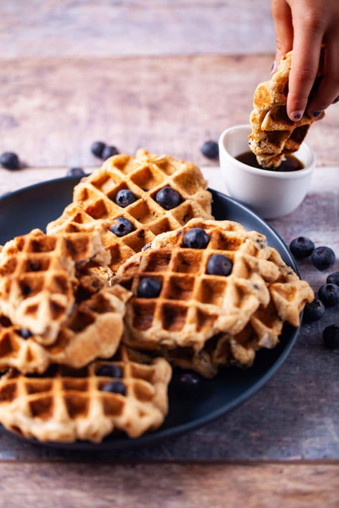 A piece of a healthy waffle dipped into maple syrup next to a stack of homemade gluten-free waffles.