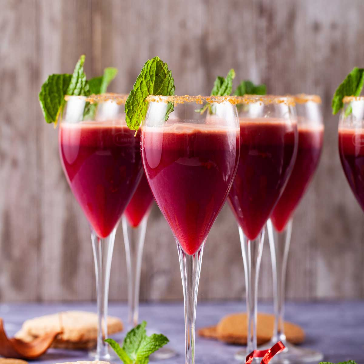 A close-up of champagne glasses with a sugary rim, filled with a red drink, garnished with mint leaves and served with cookies on the side.