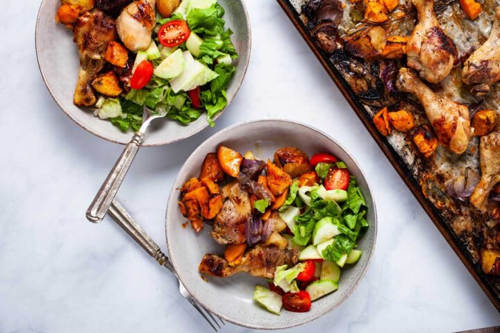 Two plates filled with roasted drumsticks, sweet potatoes and a green salad next to a chicken dinner sheet pan.