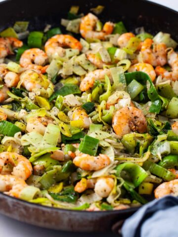 A closeup of a large skillet filled with sauteed shrimp and leeks.