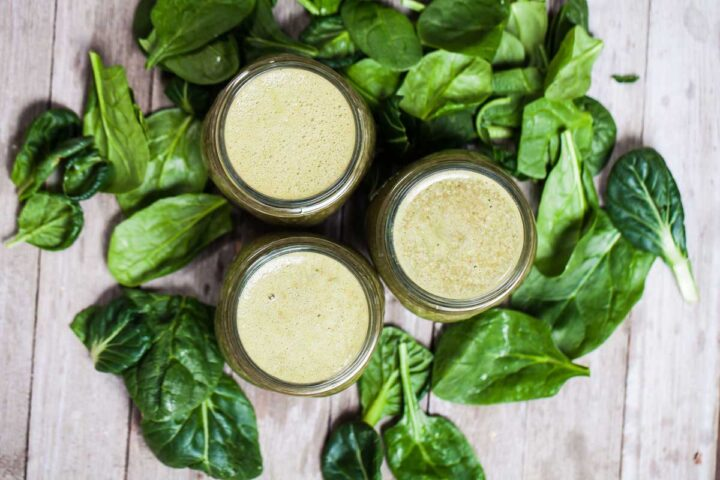 Three small glass jars filled with green smoothie and surrounded by fresh spinach leaves.
