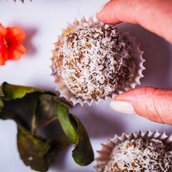A hand grabbing an energy ball sprinkled with dried coconut flakes and served in tiny paper cupcake holder.