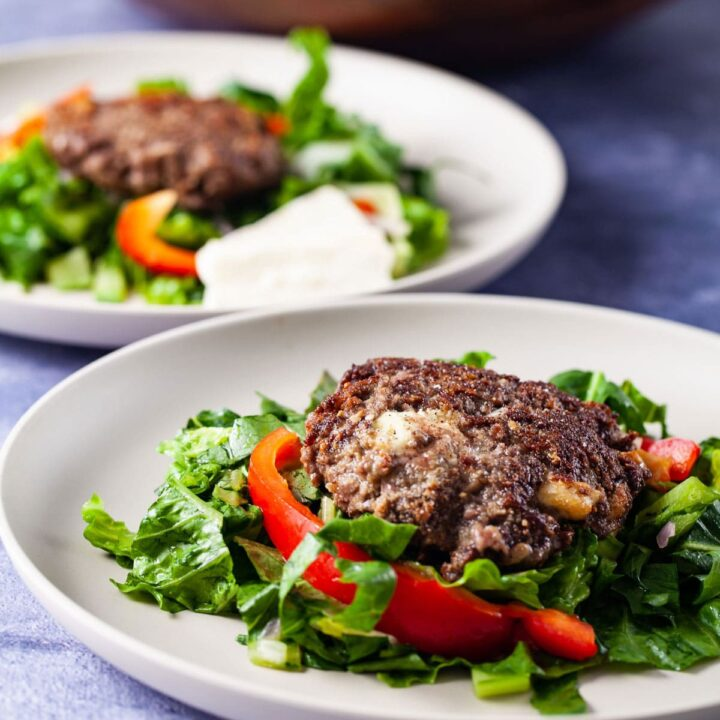 Closeup of a bunless beef burger on top of a healthy salad.