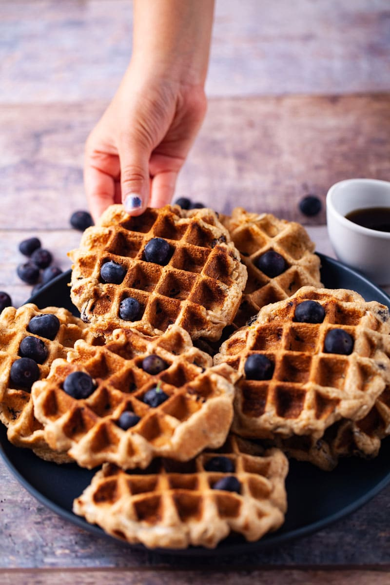 Healthy gluten-free oat flour waffle taken from a stack topped with blueberries