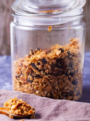 Baked granola stored in a wide-mouth glass jar.