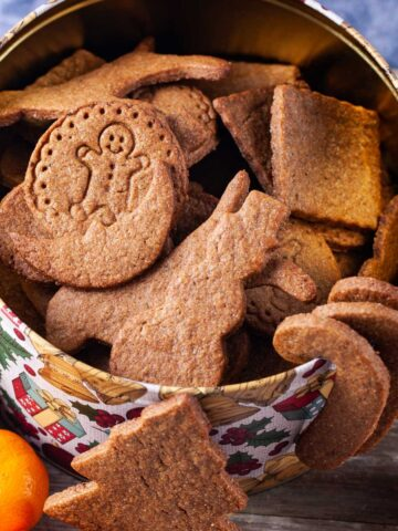 Different shaped brown cookies in a large Holiday cookie box.