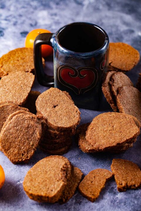Stacked brown cookies laid out around a dark blue coffee much with a red heart shape.