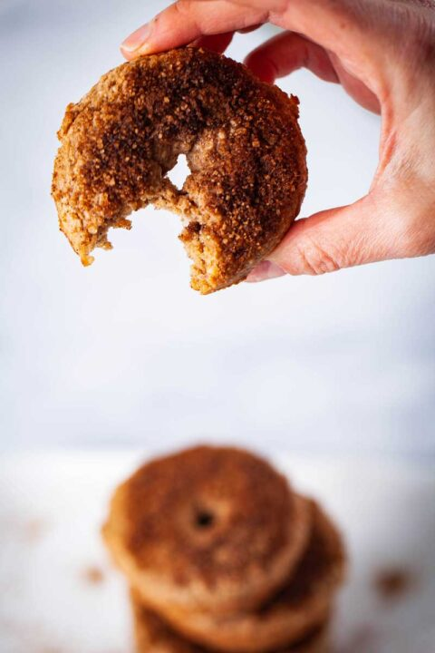 A close-up of a hand holding up a cinnamon sugar topped gluten-free doughnut with a bite in it.