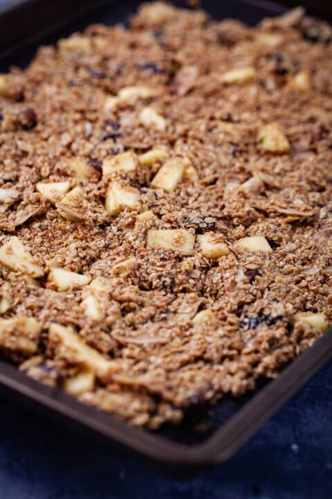 Unbaked homemade granola spread out on a large baking tray.