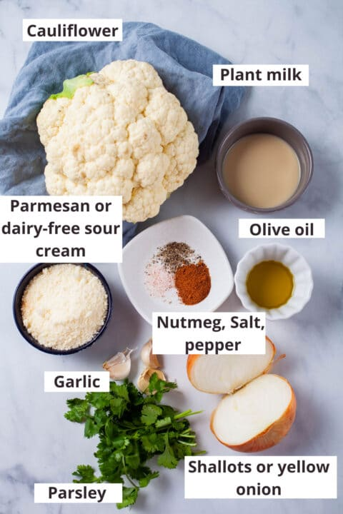 Ingredients like cauliflower, plant milk, olive oil, parmesan cheese, nutmeg, salt, pepper, garlic, parsley, and half of a yellow onion displayed on a table.