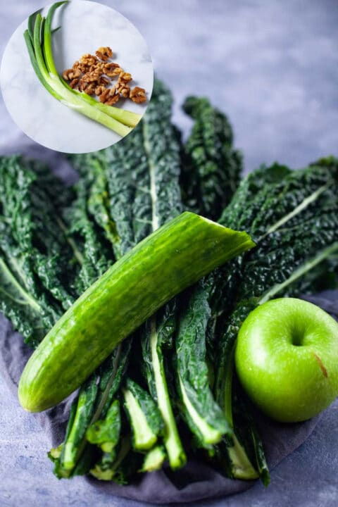 Fresk kale leaves, half a cucumber, a green apple, green onions, and chopped walnuts shown on a white background.