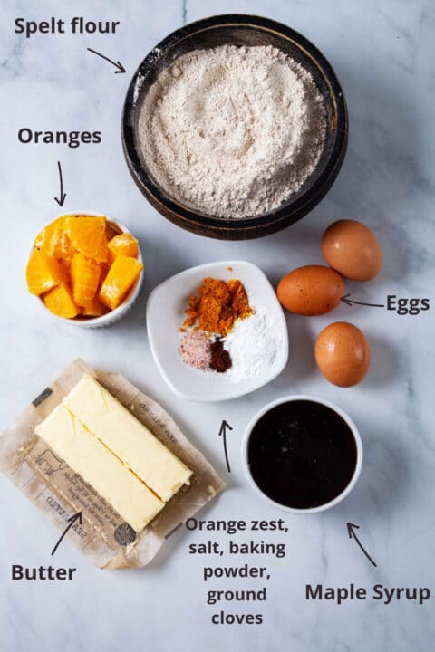 Ingredients like spelt flour, diced oranges, eggs, butter, maple syrup, orange zest, and spices displayed on a table.
