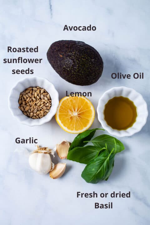 Ingredients such as avocado, roasted sunflower seeds, olive oil, lemon, garlic, and fresh basil laid out on a board.