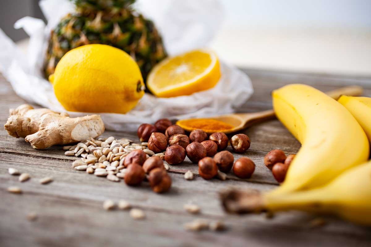 Ingredients like lemon, banana, pineapple, turmeric, ginger, hazelnuts and seeds for making a healthy creamy smoothie