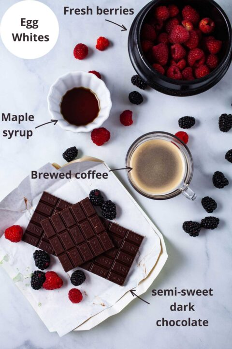 Ingredients such as egg whites, fresh berries, maple syrup, brewed coffee, and semi-sweet dark chocolate laid out on a white background.