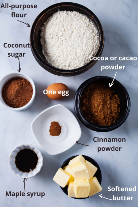 Ingredients like all-purpose flour, coconut sugar, cacao powder, an egg, cinnamon powder, maple syrup, and softened butter displayed on a table.