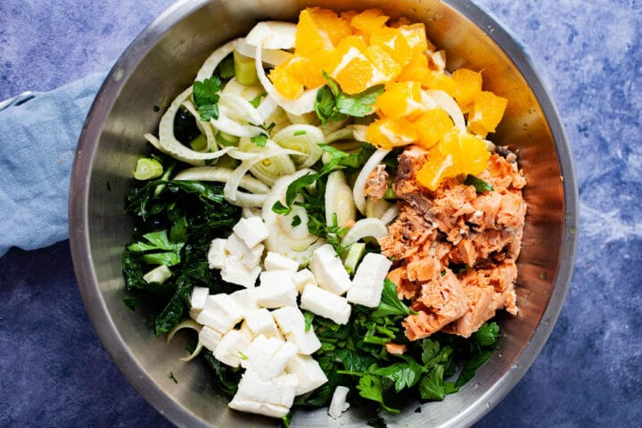 A bowl filled with raw chopped green kale, canned salmon, fennel, oranges, parsley, and mozzarella cheese.