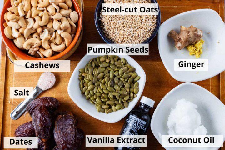 Ingredients to create a no-bake tart crust on a cutting board: cashews, steel-cut oats, fresh ginger, pumpkin seeds, salt, Medjool dates, vanilla extract, and coconut oil.
