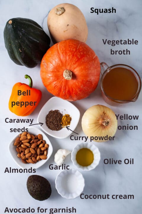 Ingredients like squash, broth, onion, olive oil, bell pepper, almonds, garlic, coconut cream, avocado, and spices displayed on a table.