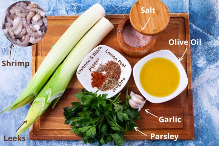 Shrimp, leeks, parsley, garlic, olive oil, salt, cayenne and black pepper, lemon peel, and dried oregano, all ingredients shown to make a garlic shrimp dish.