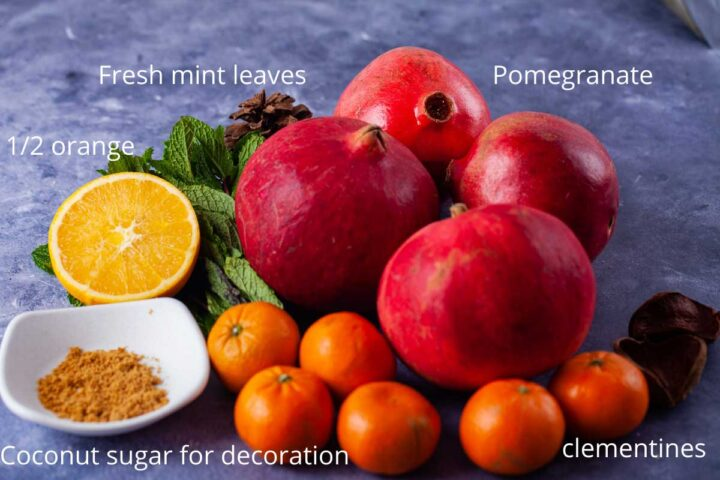 Ingredients to make a non alcoholic drink: pomegranate, fresh mint leaves, half an orange, coconut sugar, clementines.