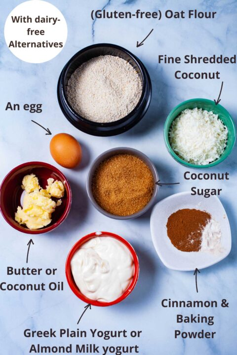 Ingredients to make baked doughnuts: oat flour, fine shredded coconut, coconut sugar, cinnamon and baking powder, plain yogurt or almond yogurt, butter or coconut oil, and an egg.