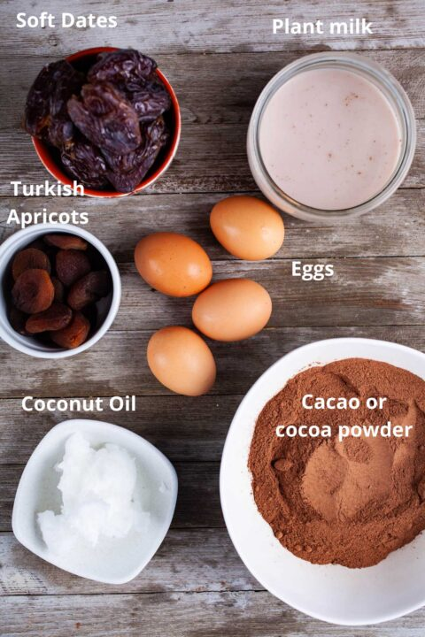 Ingredients such as soft dates, plant milk, Turkish apricots, eggs, coconut oil, and cacao or cocoa powder all separately spread out on a wooden board.