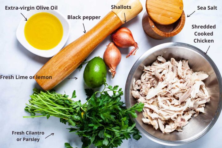 A display of ingredients such as Extra virgin olive oil, a black pepper corn mill, shallots, sea salt, shredded cooked chicken, a fresh lime, and fresh cilantro leaves.