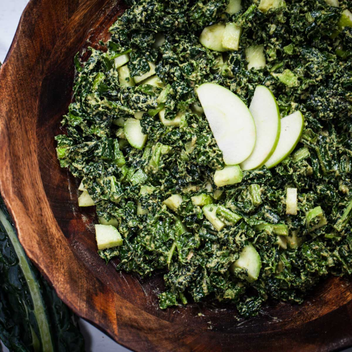 A massaged apple kale salad in a large wooden bowl.