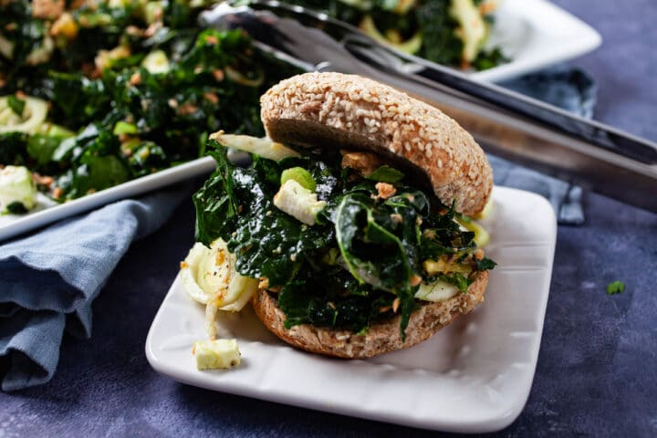 A seed bun generously filled with kale salmon salad served on a small plate.