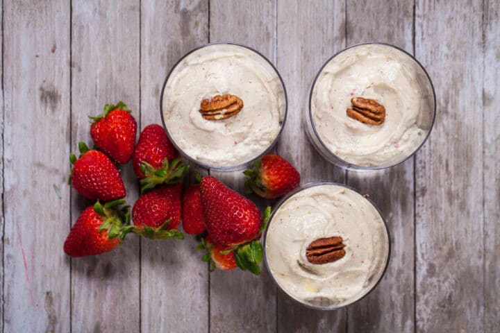 Three glass cups on a wooden board filled with creamy avocado strawberry cream, topped with pecan halves next to fresh strawberries.