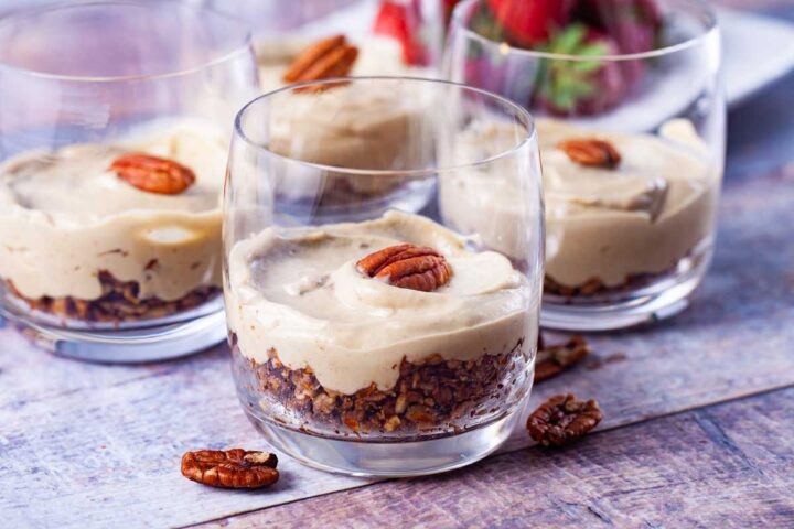 Four individual glass cups with crumble at the bottom and a cheesecake layer topped with pecan halves.