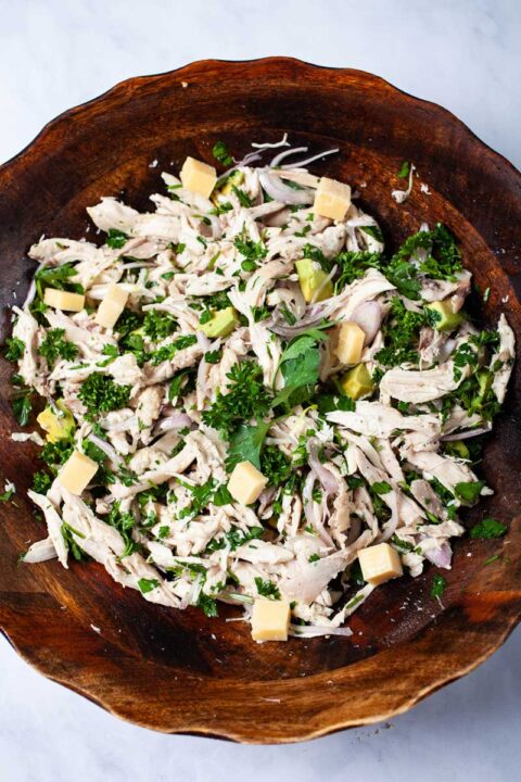 A large deep wooden bowl filled with shredded chicken salad with chopped cilantro, chopped parsley, olive oil, sliced shallots, salt and pepper, cubed avocado, and cubed hard cheese.