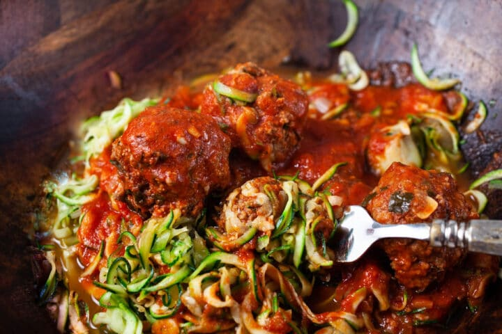 A large wooden bowl filled with raw zucchini noodles topped with an Italian red spaghetti sauce and beef meatballs.