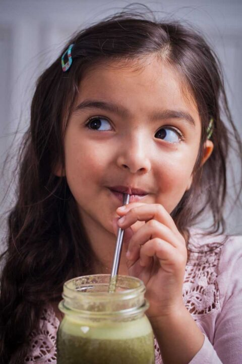 A smiling girl drinking a smoothie from a stainless steel straw.