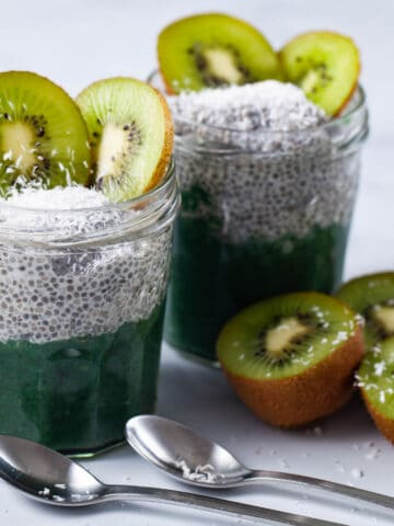 Two jars filled with chia pudding, infused with a kiwi sauce, topped with coconut shreds, and slices of fresh kiwi.