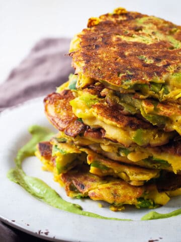 A stack of Crispy Vegetable Fritters with a pesto sauce