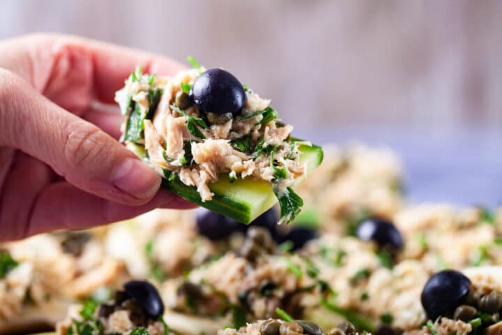 A hand holding a thick cucumber slice topped with creamy tuna and parsley salad and garnished with dark grapes.