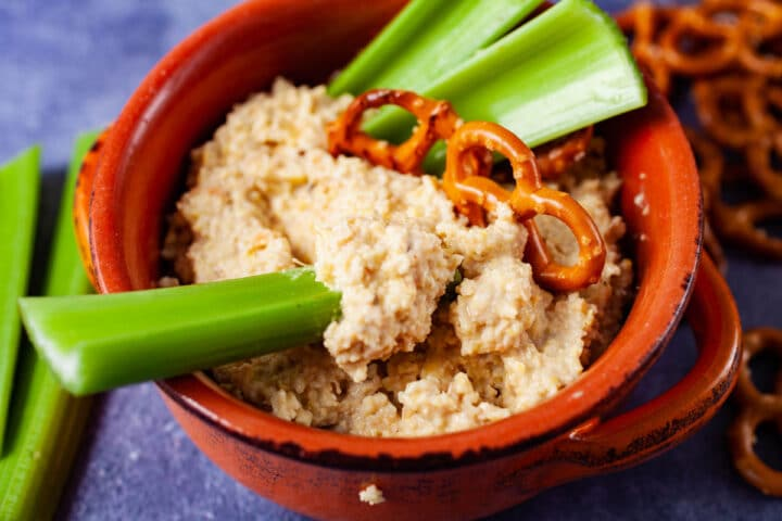 A terra cotta bowl filled with Lupin Hummus and topped with pieces of celery, and pretzels.