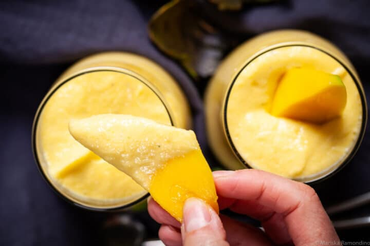 A hand holding a slice of fresh mango over a glass half dipped with mango lassi.