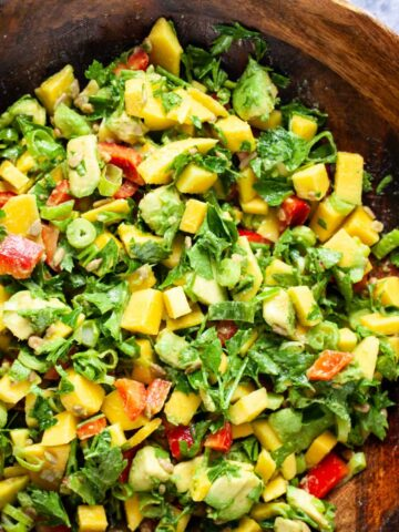 A large wooden bowl filled with fresh and creamy mango avocado salad, onions, cilantro, sunflower seeds and red bell peppers.