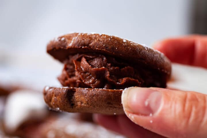 A close-up of a hand holding a mascarpone filled sandwich cookie.
