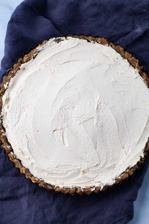 A large round tart with a no bake crust and equally filled with mascarpone cheese.