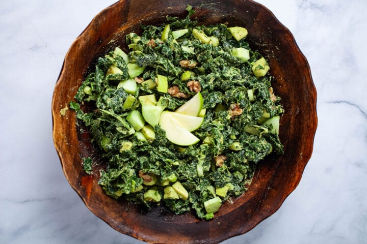A wooden bowl filled with a creamy apple kale salad.